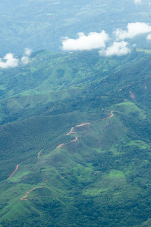 aerial view of the mountain landscape with lush green vegetation and a dirt road across the top of the mountains