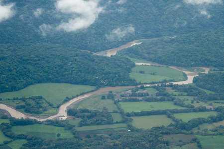 bird 's eye view: dense green vegetation with a rushing river seen from above during a local flight across Costa Rica