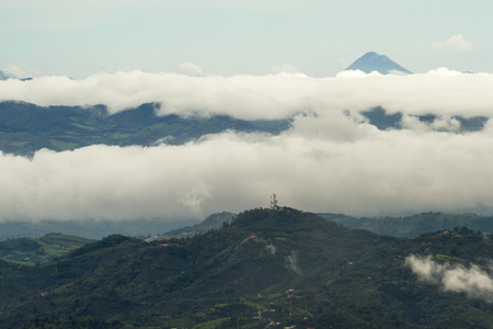 peaking: aerial view of the Arenal Volcano in Costa Rica peaking thru the clouds Stock Photo