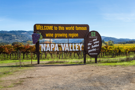 sight seeing: view of the napa valley welcome sign with color changing grape vines in the background in autumn