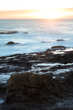 slow motion: rough seas captured with a slow shutter speed creating a relaxing scene with water flowing over the lava rock with a smooth motion effect