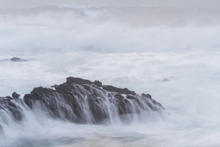 coastal scene in California using a slow shutter speed with waves crashing onto the lava rock Stock Photo