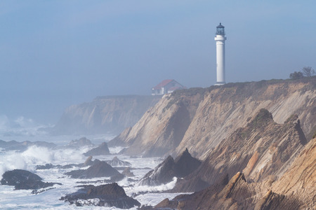 seas: foggy afternoon with rough seas crashing onto the rocks and the Lighthouse at Point Arena in the background