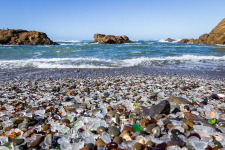 Beautiful sea glass in a variety of colors with blue waves and sky in Fort Bragg, California