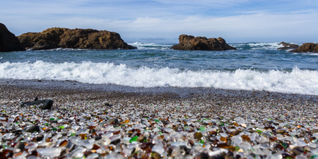 colorful glass pebbles blanket this beach in Fort Bragg, California, photo taken mid day to get bright color in the rocks and water