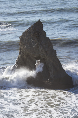 powerful waves crashing against a large rock with a hole in the middle Stock Photo