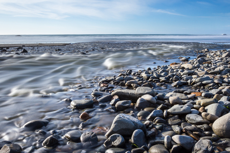 silky water flowing over the rocky shore making its way to the ocean