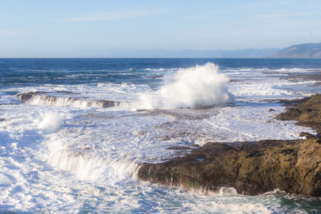 peaceful and relaxing scene with waves crashing against the rocky shore line of a beach in California