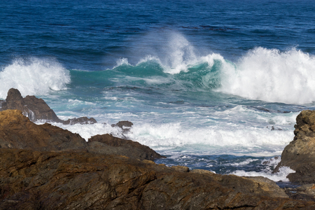 beautiful deep blue water with turquoise waves coming to a rocky shore Stock Photo