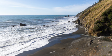 rocky shoreline with rows of waves crashing into the mountain in the northern California coast Stock Photo