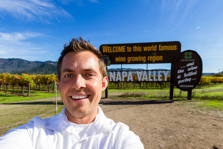 young man taking a self portrait with the Napa Valley welcome sign in the background