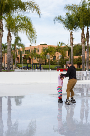 teaching stations: San Diego, California - November 26: Father teaching his little girl how to ice skate in southern California. November 26 2016, San Diego, California.