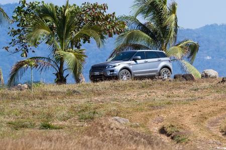 Puntarenas, Costa Rica - February 25: Range Rover Evoke parked under palm trees in a dry rocky cliff in Costa Rica. Puntarenas, Costa Rica - February 25 Editorial