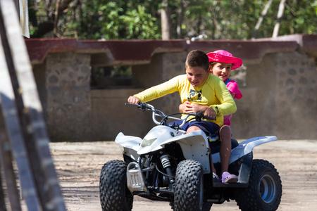 Junquillal, Guanacaste, Costa Rica - April 10: Young children riding a four wheeler near the beach. April 10 2017, Junquillal, Guanacaste, Costa Rica. Editorial
