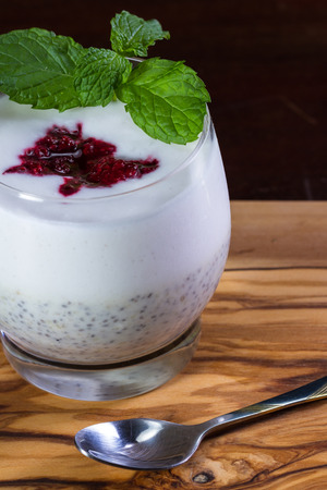 close up of a glass with  banana chia seed pudding layers with a raw coconut milk yogurt with a dollop of mashed berries on top