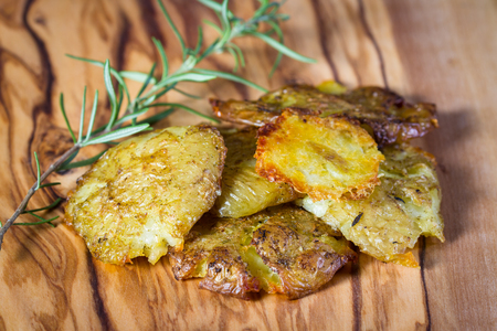 serving of potatoes that have been smashed and then baked with seasoned oil and spices as a side dish Stock Photo