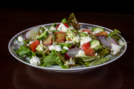 refreshing green salad with fresh goat cheese, tomatoes, cucumbers and radishes