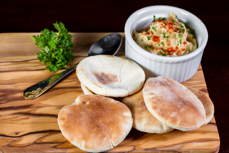 dipping: ramekin filled with hummus topped with paprika and parsley as a garnish served with small pita bread rounds served on a wooden board Stock Photo