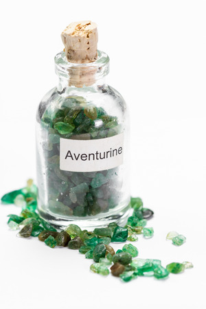 energy healing: close up of a jar filled with green aventurine, a crystal meant to increase ones opportunity, wealth and luck.