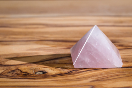 close up of a rose quartz pyramid on a wooden background, this stone is known as the stone of the heart, and promotes unconditional love. Imagens