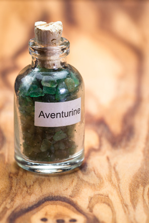 close up of a jar filled with green aventurine, a crystal meant to increase ones opportunity, wealth and luck.