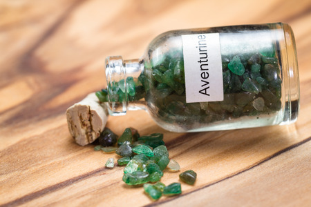 increasing: close up of a jar filled with green aventurine, a crystal meant to increase ones opportunity, wealth and luck.