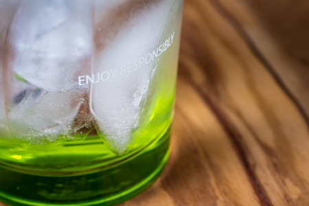 concept for drinking responsibly with the words enjoy responsibly edged on a glass with an alcoholic beverage in it