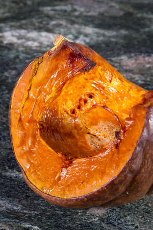 quarter of a pumpkin oven roasted until tender placed on a granite countertop