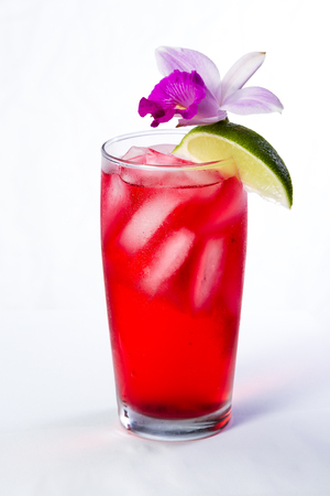 red cocktail garnished with a bamboo orchid and a lime  isolated on a white background Stock Photo