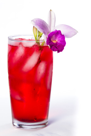 red cocktail garnished with a bamboo orchid  isolated on a white background Stock Photo