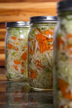 close up of a pint size jar filled with vegetables like carrots and cabbage and a probiotic bacteria to begin the fermentation process. Placed on a granite countertop.