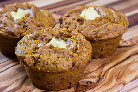 close up of a home made pumpkin muffin on a wooden background