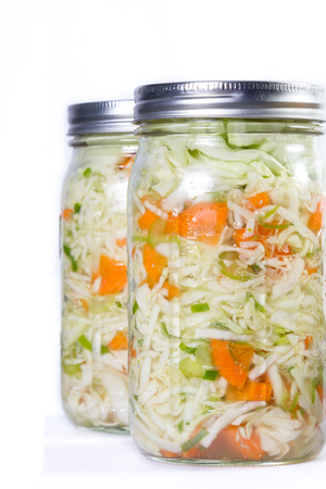 close up of a pint size jar filled with vegetables like carrots and cabbage and a probiotic bacteria to begin the fermentation process. Isolated on a white background.
