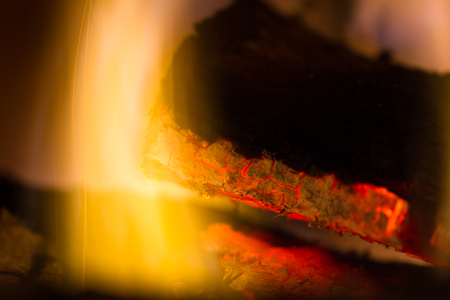 close up of glowing red embers and flames on a lot in the fireplace Stock Photo