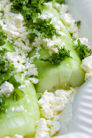 sourced: close up of a cucumber and feta cheese salad topped and dressed with parsley and green onion with lemon juice and olive oil