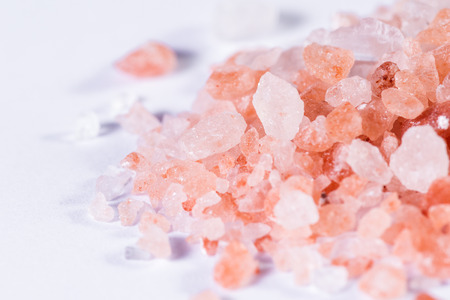 Himalayan pink salt crystals piled and isolated on a white background