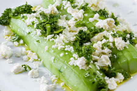 close up of a cucumber and feta cheese salad topped with green onion and parsley dressed with olive oil and lemon juice
