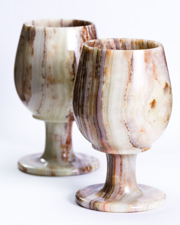 grounding: close up of a set of beautiful onyx cups with unique swirls and layers isolated on a white background