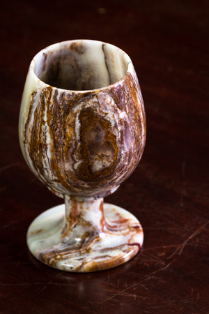 close up of a beautiful Onyx chalice on a dark wooden table Stock Photo