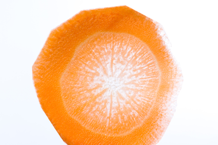 close up of a thin slice of carrot back lit with a beautiful pattern and glowing orange color