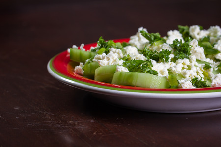 sourced: close up of a cucumber and feta cheese salad topped with green onion and parsley dressed with olive oil and lemon juice