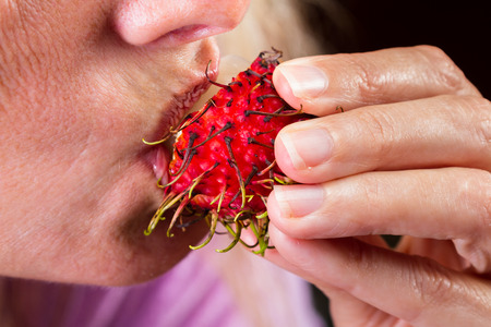 close up of a womans hand and mouth eating a rambutan