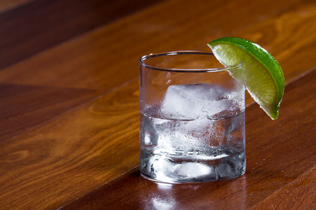 close up of a glass with a cube of ice and clear alcohol garnished with a lime on the rim of the glass served on a wooden bar top Stock Photo