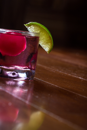 refreshing drink with a red ice ball releasing flavor into the cocktail as it melts and chills the beverage garnished with a lime wedge on the rim of the glass Stock Photo