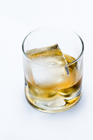 blended scotch whiskey served in a short glass with a large ice cube isolated on a white background Stock Photo