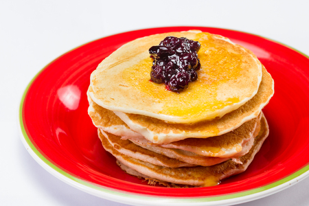 stack of pancakes served on a red plate with a blueberry compote on top