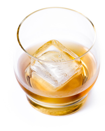 tasty single malt scotch whiskey served with a large ice cube isolated on a white background Stock Photo