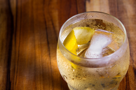 refreshing scotch and soda served on the rocks with a lemon twist on a wooden bar top