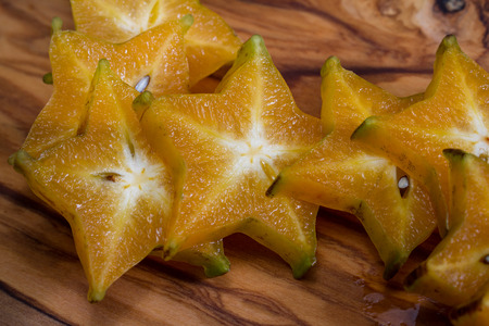 close up of a ripe sliced carambola or starfruit on a wooden cutting board Stock Photo