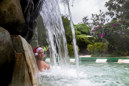young man relaxing in natural hot springs in Costa Rica wearing a red seasonal hat